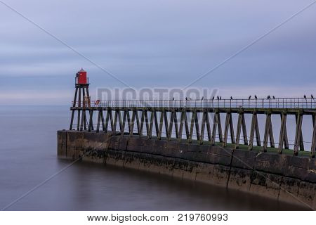 Whitby harbour entrance east pier and beacon North Yorkshire England.