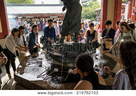 Tokyo - Japan, June 17, 2017; Purify hands and mouth at the temizuya, water pavilion, in front of Senso ji Temple in Asakusa