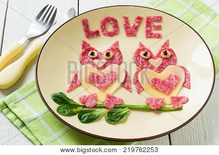 Decoration of food for Valentines Day. Appetizer of cheese and sausages. Two loving owls made up of edible hearts. Inscription love cut out of salami. Symbols of Valentines Day in design