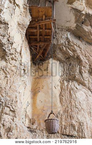 Near Mitzpe Yeriho Israel November 25 2017 : A hermit's basket for raising food in the caves of the monastery of St. George Hosevit (Mar Jaris) in Wadi Kelt near Mitzpe Yeriho in Israel
