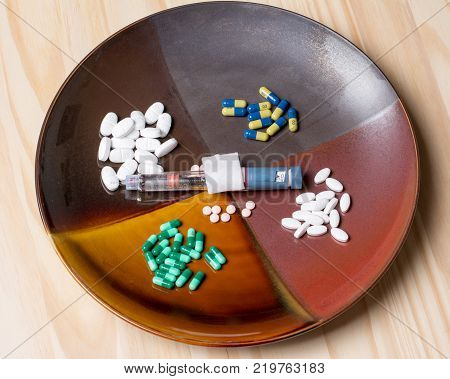 assortment of pills on a dinner plate representing our modern day need to self medicate.