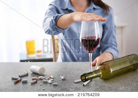 Young woman covering glass of wine with hand while sitting at table. Concept of refusing from bad habits
