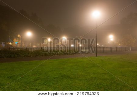 Empty park and streetlights at foggy night