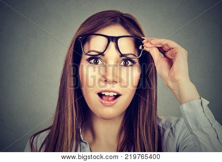 Surprised girl taking off her glasses isolated on gray wall background