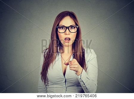 Closeup portrait shocked business woman looking surprised saw something pointing finger at camera isolated on gray wall background.