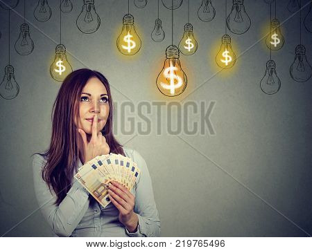 Portrait thinking young woman holding money looking up at dollar idea light bulbs above head