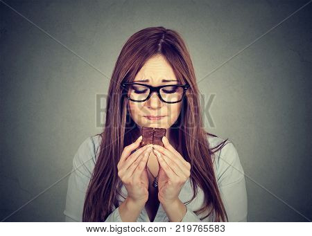Portrait sad woman tired of diet restrictions craving sweets chocolate isolated on gray wall background. Human face expression emotion. Nutrition concept. Feelings of guilt