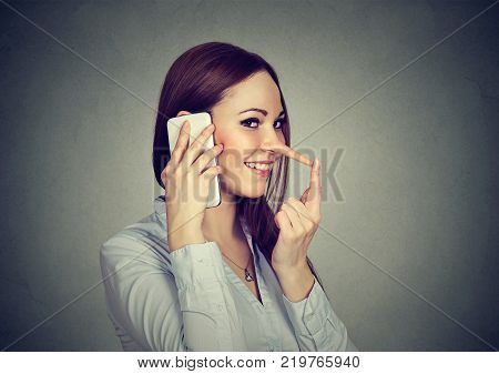 Happy young woman with long nose talking on mobile phone isolated on gray wall background. Liar concept. Human emotion feelings character traits