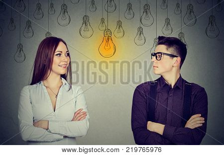 Cognitive skills ability concept male vs female. Young man and woman looking at bright light bulb each other isolated on gray wall background