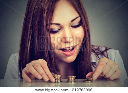 Young woman counting money stacking up coins