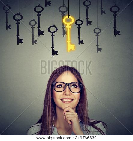 Beautiful thoughtful woman looking upSmiling woman looking up at vintage golden key to success among many others hanging. Concept of business aspirations achievement