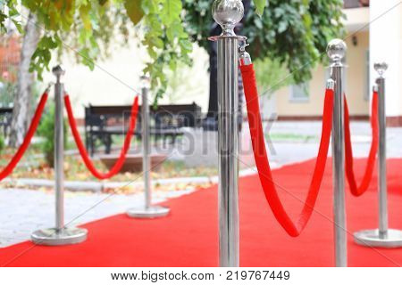 Rope barrier on red carpet, outdoors