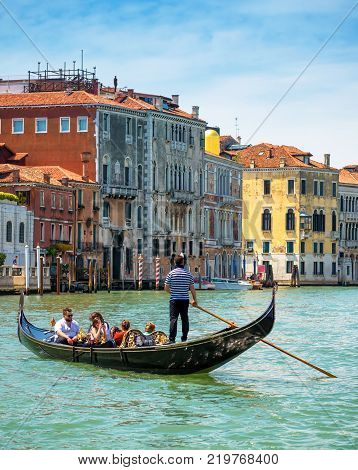 Venice, Italy - May 19, 2017: Gondolas with tourists are sailing along the Grand Canal. Gondola is the most attractive tourist transport in Venice.