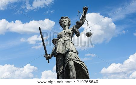 The Statue of Justice - lady justice or Iustitia / Justitia the Roman goddess of Justice against blue cloudy sky. ideal for websites and magazines layouts