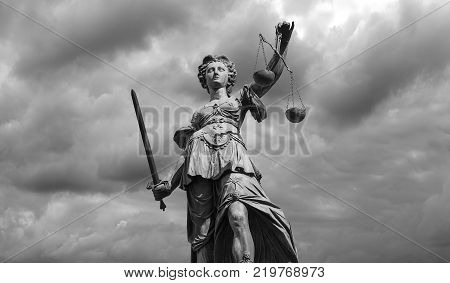 The Statue of Justice - lady justice or Iustitia / Justitia the Roman goddess of Justice against dramatic cloudy sky. ideal for websites and magazines layouts