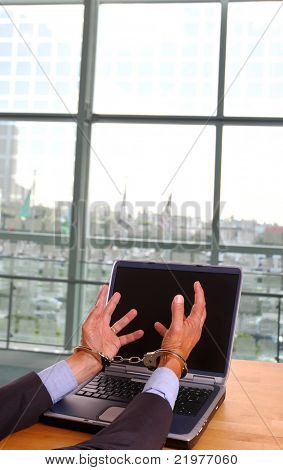 Businessman's handcuffed hands reaching towards laptop computer screen in office setting