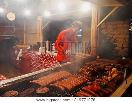 Poznan, Poland - 02 December 2017: People fry grilled sausages on big hanging grill at Christmas market in Poznan