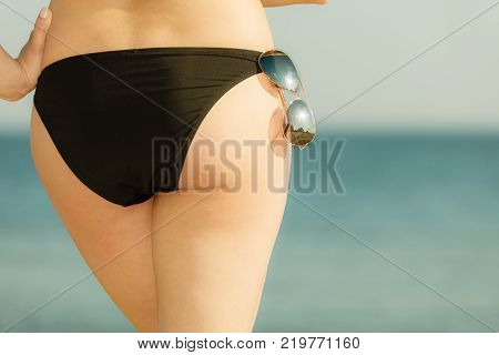 Summertime underwear being confident during summer concept. Woman bottom bum in black bikini panties and glasses. Sea background. poster