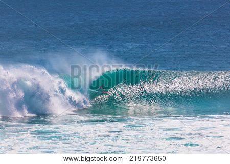 Surfer riding very big wave at Uluwatu beach, Bali, Indonesia