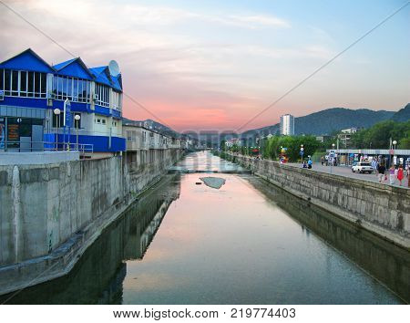 OLGINKA, RUSSIA - June 25, 2011: Tourists walk along the river channel Tu in the evening at sunset.