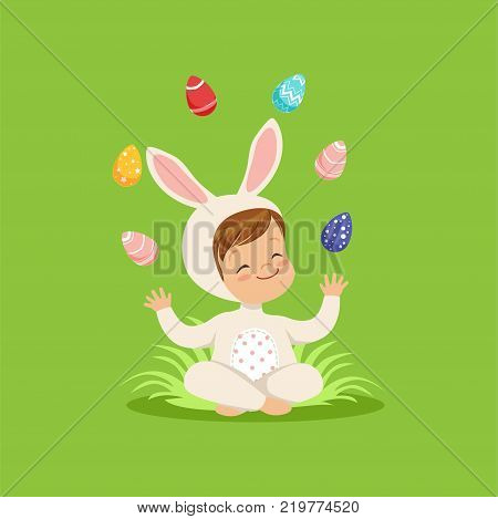 Cute little boy in bunny costume sitting on the grass juggling with painted eggs, kid having fun on Easter egg hunt vector Illustration on a lawn green background