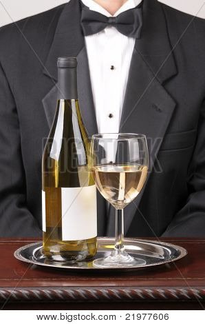 Waiter wearing a tuxedo with a White Wine Bottle With Blank Label and Glass on Silver Tray and Wood Table over a gray background vertical format