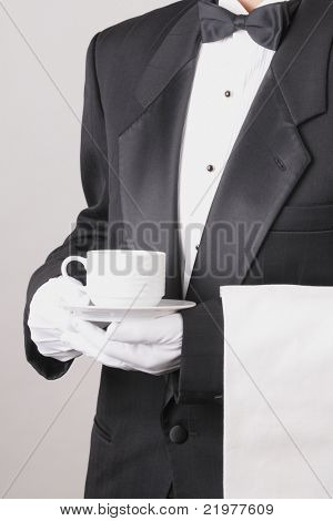 Waiter in Tuxedo holding a coffee cup with a towel draped over his arm torso only vertical format over gray background