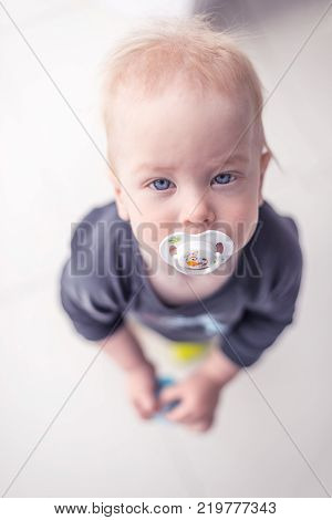 Sweet baby girl with a soother standing on floor