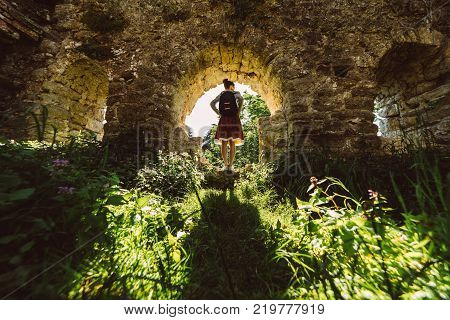 Young woman traveler in skirt standing in ancient temple with green plants  frame,looking around,summer travel vacations