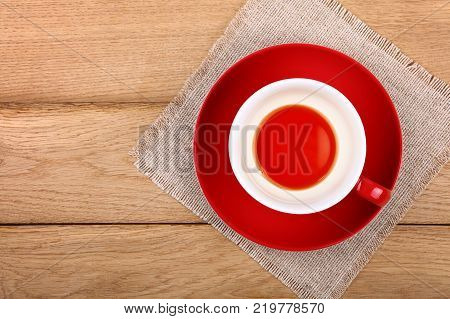 Empty finished cup of black tea on red porcelain saucer over wooden table with textile tablecloth napkin close up elevated top view directly above