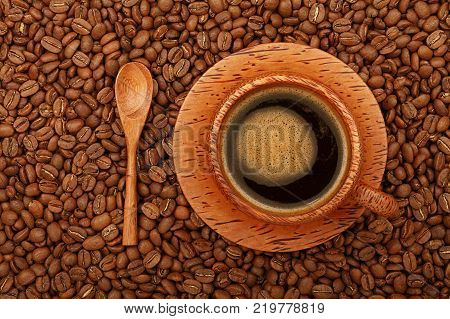 Brown coconut palm carved wood cup full of black coffee with froth on wooden saucer and spoon over background of roasted coffee beans elevated top view directly above