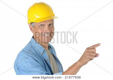 Construction worker wearing a yellow hard hat pointing while he smiles at the camera. Closeup in horizontal format isolated on white.