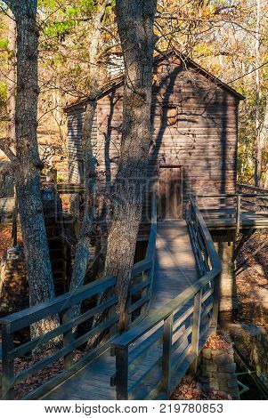 Grist Mill and the wooden bridge in the Stone Mountain Park in sunny autumn day Georgia USA
