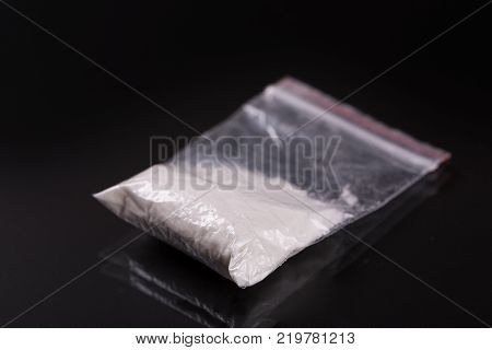 Cocaine in plastic packet on black background, closeup