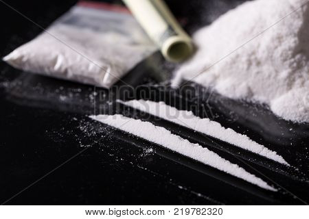 Rolled hundred dollars banknote, two lines and pile of cocaine on black background, closeup