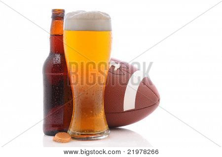 American Football behind a bottle and glass of beer with condensation. Horizontal format on a white background with reflection.
