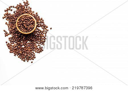 Fresh roasted coffee beans in bowl on white table top view copyspace. Coffee background