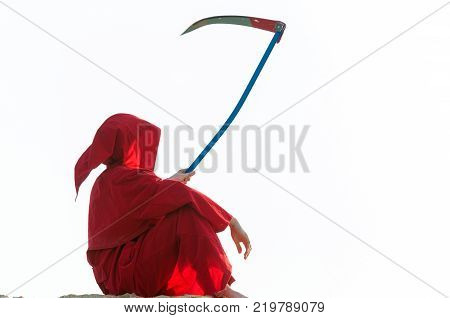 Spooky figure in red cloack with scythe