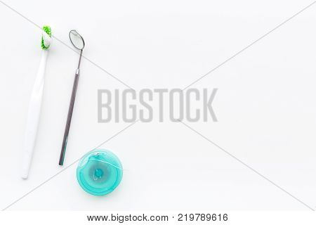 Healty teeth. Toothbrushes and dental mirror on white background top view.