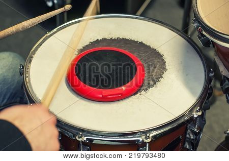 Drummer fulfills skills on the training pad. Selective focus.