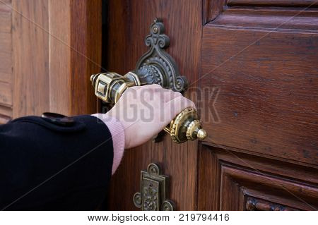 A female hand holding a crank from an old wooden door and opening