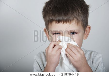 sick child blows his nose in a handkerchief