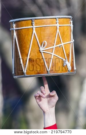 The musician rotates Dhol on one finger. Dhol can refer to any one of a number of similar types of double headed drum widely used, with regional variations, throughout the Indian subcontinent.