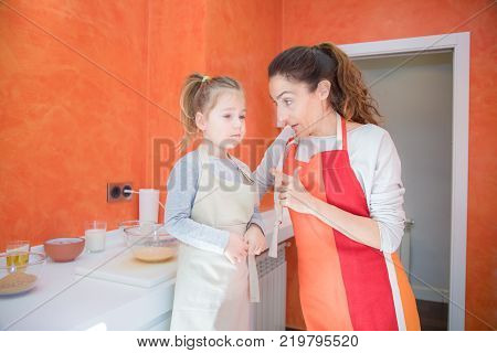 Child Cooking And Looking At Mother In The Kitchen