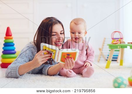 cute mother and daughter playing together reading first book