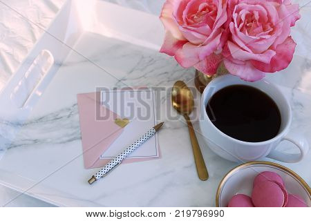 Pink and white styled breakfast tray with coffee, flowers and stationary.