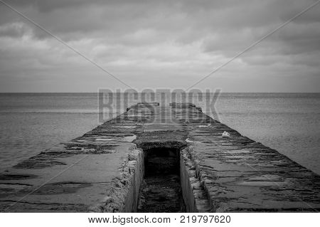 Ocean landscape in bad weather. Ocean horizon. Cloudy sky over the ocean. Stone ocean pier. Black and white photography.