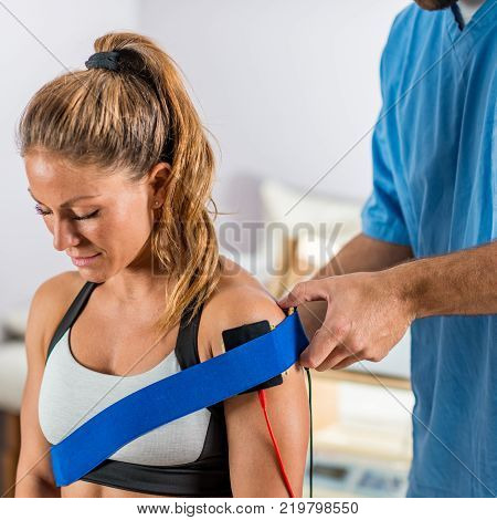 Electrical stimulation in physical therapy. Therapist positioning electrodes on a patient's shoulder. Woman patient