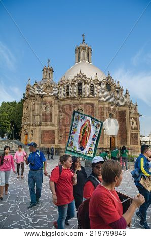 VILLA OF GUADALUPE MEXICO CITY DECEMBER 02 2017 - Pilgrims from the Teofani region in Hidalgo Mexico carry a banner with the image of the Virgin of Guadalupe in front of the Temple of the Pocito.