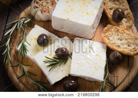 Greek feta cheese, famous dairy product with black olives and rosemary